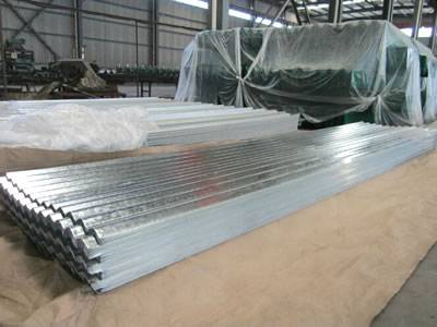The Picture Shows Many Galvanized Corrugated Sheets Piled Together Near A  Machine In The Warehouse.