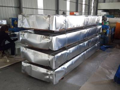 The picture shows four packages of steel roof tiles in the warehouse.